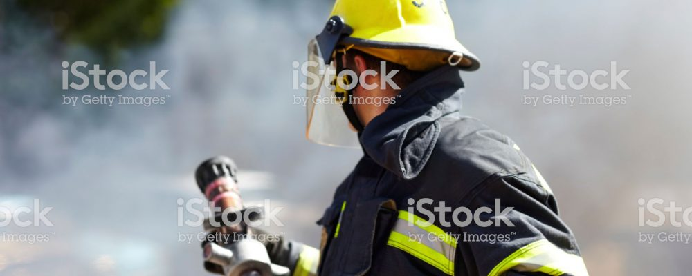 A caucasian fireman holding a hose and surrounded by the smoke from the fire he's just extinguished