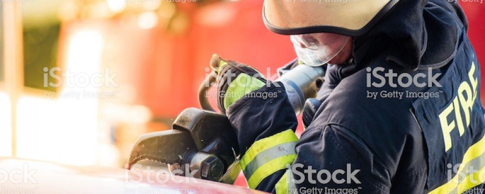 Rescue services cutting car windscreen with breaker.